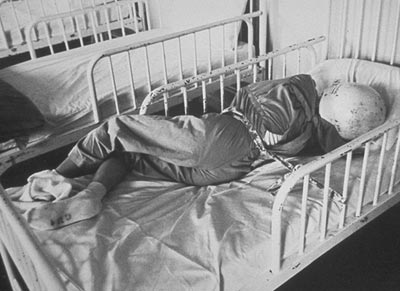 Child chained in bed wearing protective headgear and mask