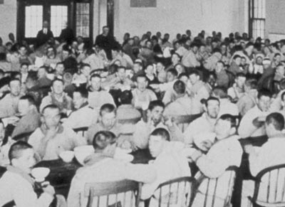 Hundreds of inmates gather for a meal in an institution, circa early 1900s