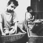 Children waiting, sitting in wooden boxes, circa 1960