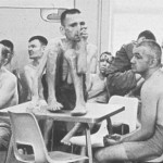 Poorly clothed residents gather in the day room of an institution, circa 1960s