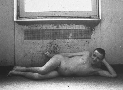 Unclothed male resident of an institution lies before a radiator, circa 1960s