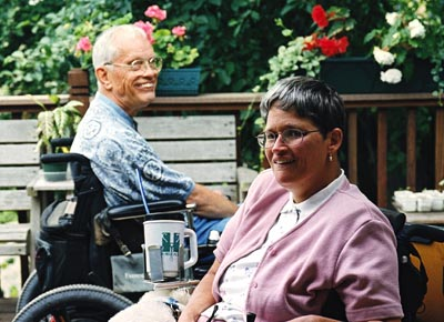 Man and woman sitting in wheelchairs on the deck of their home