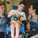 Mother and father kneel on either side of a young boy in a wheelchair who is playing with a toy in the hallway of a hospital.