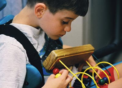 Young boy in a wheelchair examines a toy.