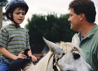 Young boy wearing a riding helmet sits on a horse being held by his father.