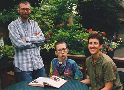 Mother, father and son sit on a deck on a summer day. The boy is seated in a wheelchair, reading a book.