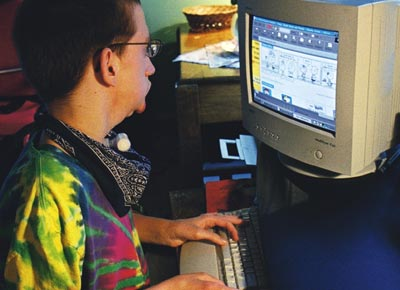Boy in a wheelchair using a computer in his home.