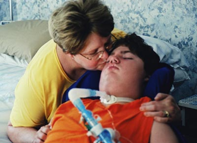 Mother kissing a young man with significant disabilities in the bedroom of a home.