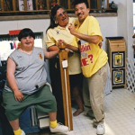 Smiling young man with disabilities seated on the floor with two young girls, a woman and a dog.