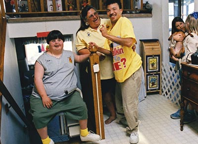 Woman laughs with a young man and a young woman with disabilities seated on a lift at the top of a flight of stairs in a home.